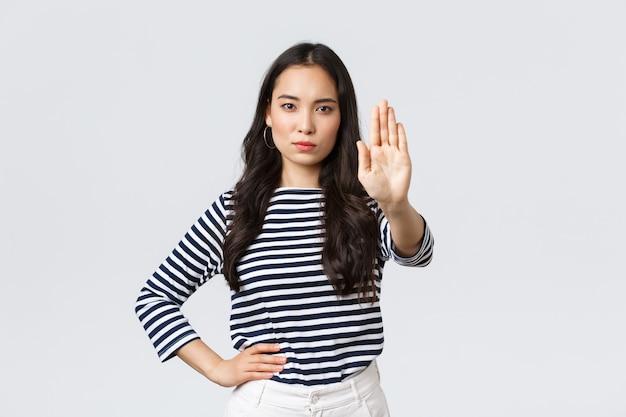 Lifestyle, beauty en mode, mensen emoties concept. serieus uitziende ontevreden aziatische vrouw zegt dat ze moet stoppen, hand teleurgesteld uitsteekt om iets ergs te verbieden of te beperken