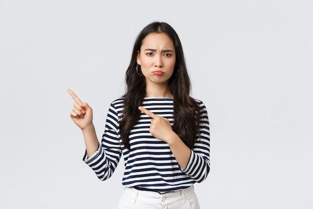 Lifestyle, beauty en mode, mensen emoties concept. teleurgesteld verdrietig aziatisch meisje dat klaagt, spijt of jaloezie voelt terwijl ze ongemakkelijk pruilt en met de vingers naar de promobanner wijst