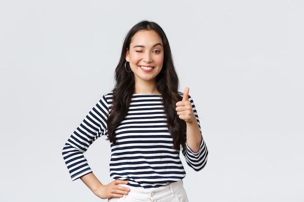 Lifestyle, beauty en mode, mensen emoties concept. vrolijk schattig aziatisch meisje duim omhoog in goedkeuring, knipoog bemoedigend en glimlachend, prees goed werk, zeg goed gespeeld als feliciteer met overwinning