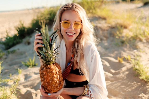Lifestyle buiten foto van lachende mooie vrouw met sappige ananas ontspannen op zonnig strand. trendy zomeroutfit