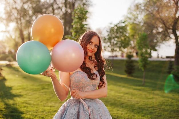 Lifestyle close-up portret van een jonge vrouw in een slimme blauwe geborduurde jurk met kleurrijke ballonnen...