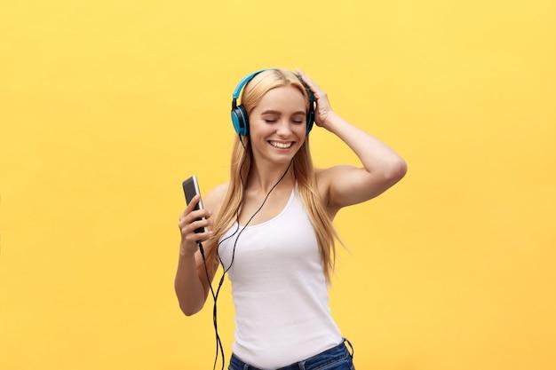 Lifestyle-concept: portret van een vrolijke vrouw in wit t-shirt en luisteren naar muziek
