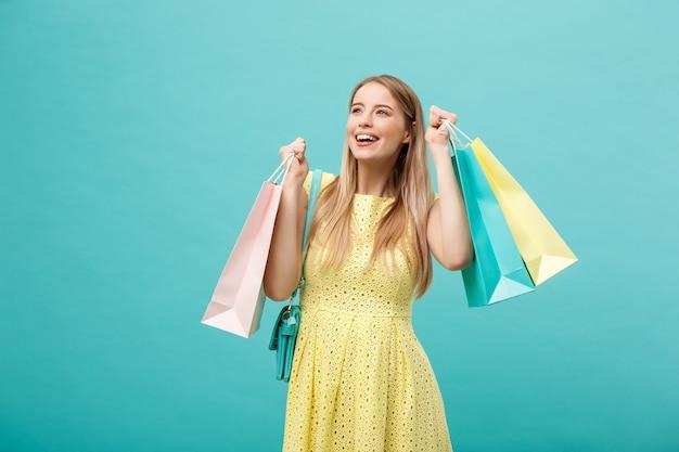 Lifestyle concept: portret van geschokte jonge aantrekkelijke vrouw in gele zomerjurk poseren met boodschappentassen en camera kijken over blauwe achtergrond.