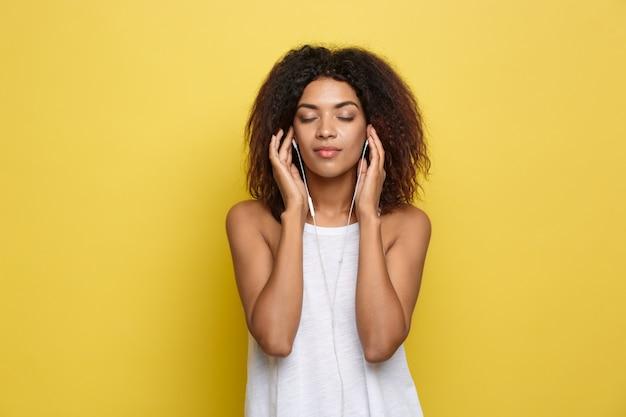 Lifestyle concept - portret van mooie afrikaanse amerikaanse vrouw blij muziek aan de mobiele telefoon te luisteren. gele pastel studio achtergrond. ruimte kopiëren.