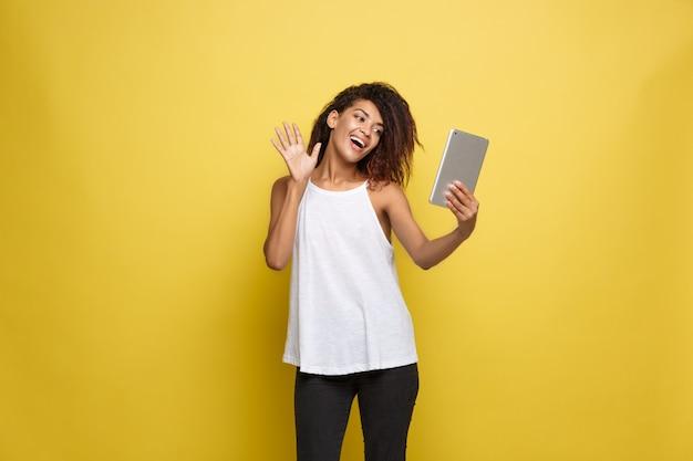 Lifestyle concept - portret van mooie afrikaanse amerikaanse vrouw blij om iets op elektronische tablet te spelen. gele pastel studio achtergrond. ruimte kopiëren.