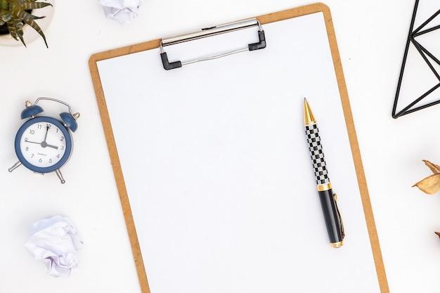 Lifestyle dingen samenstelling. kladblok met papier en pen erop, wekker. bovenaanzicht