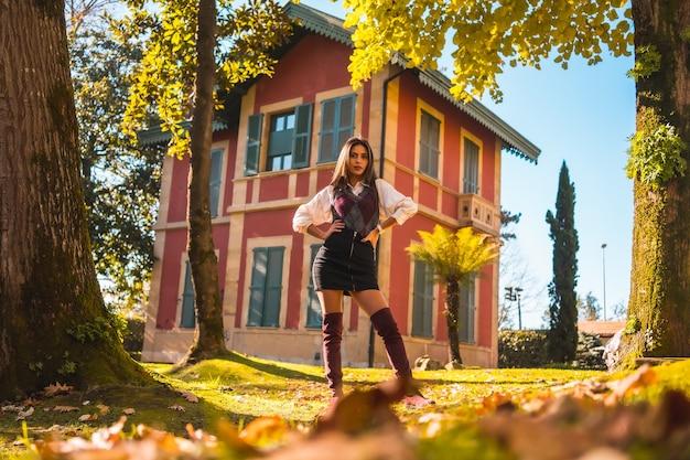 Lifestyle, een jonge blanke brunette studente, in een park naast een rood huis genietend van de herfst