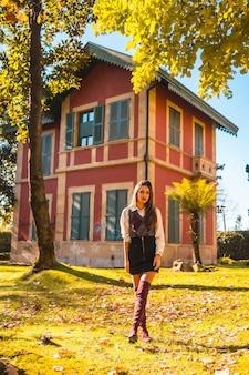 Lifestyle, een jonge blanke brunette studente, in een park naast een rood huis op een herfstmiddag in een modieuze pose