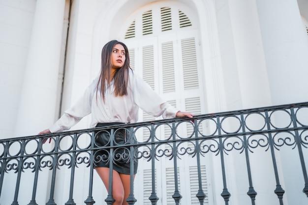 Lifestyle, een jonge brunette in een zwarte leren rok en een wit t-shirt, kijkend naar het landschap vanaf het balkon