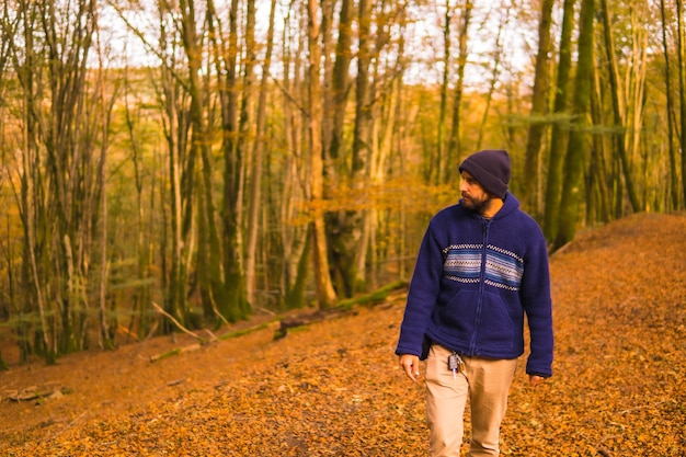 Lifestyle, een jonge man in een blauwe wollen trui die in de herfst van het bos geniet. artikutza-bos in san sebastin, gipuzkoa, baskenland. spanje
