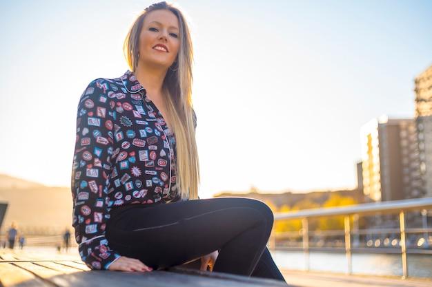 Lifestyle, een mooie blondine die geniet van de stad met huizen op de achtergrond