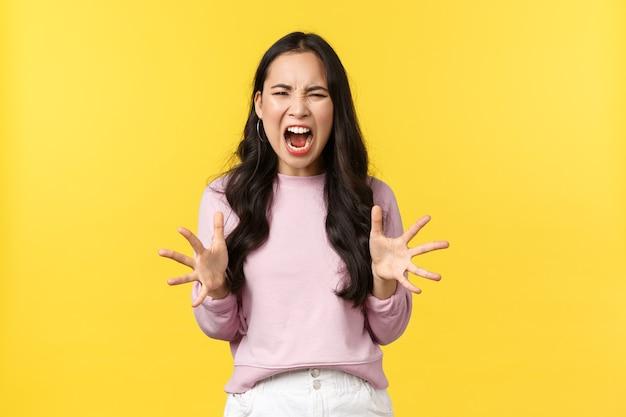 Lifestyle, emoties en advertentieconcept. gek en verontrust koreaans meisje verliest geduld, voelt zich boos en overweldigd, schreeuwt en schudt agressieve handen, staande gele achtergrond.