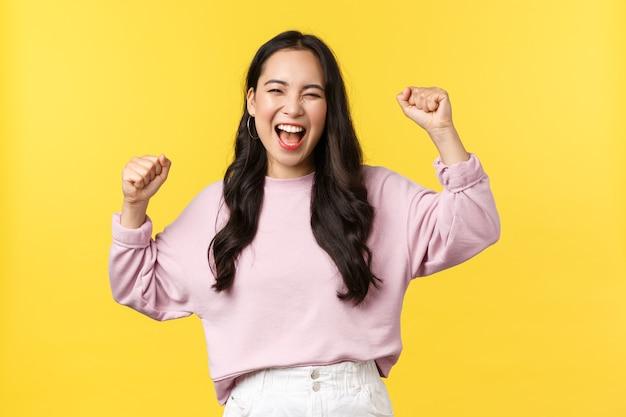 Lifestyle, emoties en advertentieconcept. gelukkig lachend en opgepompt aziatisch meisje dat de overwinning viert, ja zingt met opgeheven handen en brede grijns, triomferend over prestatie of succes.