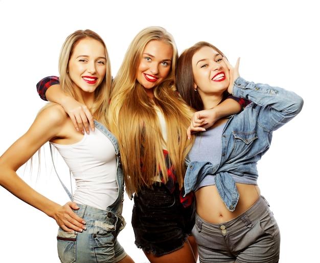 Lifestyle en mensen concept: fashion portret van drie stijlvolle sexy meisjes beste vrienden, op witte achtergrond. gelukkige tijd voor plezier.