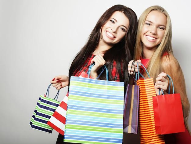 Lifestyle en mensen concept: twee jonge vrouwen dragen rode jurk met boodschappentassen. grote uitverkoop.