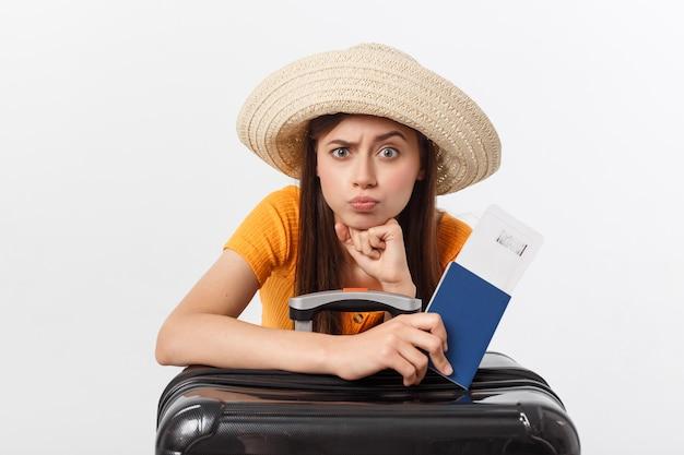 Lifestyle en reizen concept: jonge mooie blanke vrouw zit op koffer en wacht op haar vlucht. geïsoleerd over wit
