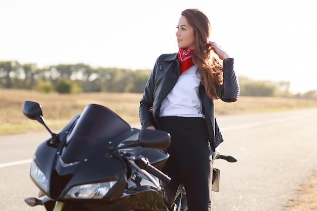 Lifestyle, extreme en mensen concept. zijdelings schot van vrij doordachte jonge vrouwelijke bestuurder gekleed in modieuze kleding, staat in de buurt van favoriete motor, poseert buiten, geniet van snel rijden