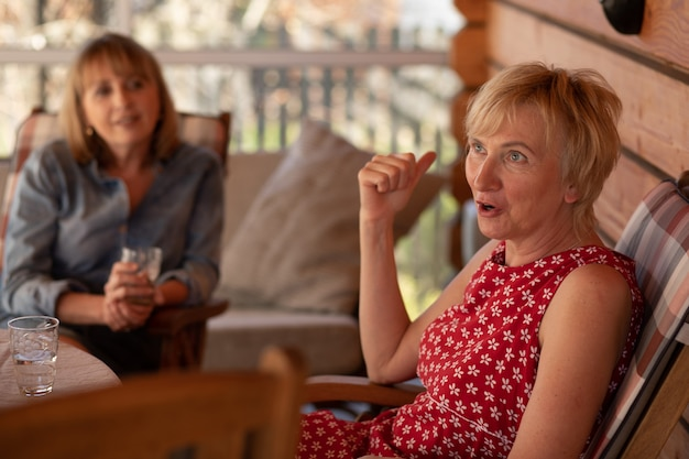 Lifestyle-foto van twee vrouwelijke zussen van 55 jaar oud, houten terrashuis