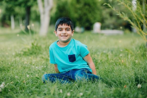 Lifestyle fotoshoot van grappige jongen met blauwe kleding zittend op gras in groene tuin