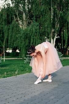 Lifestyle full-length portret van een ballerina in een roze jurk met een volle organza rok buigt zich naar...