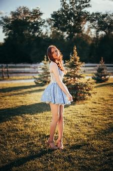 Lifestyle full-length portret van een jonge vrouw in een korte blauwe feestelijke jurk en gekruld lang haar op...