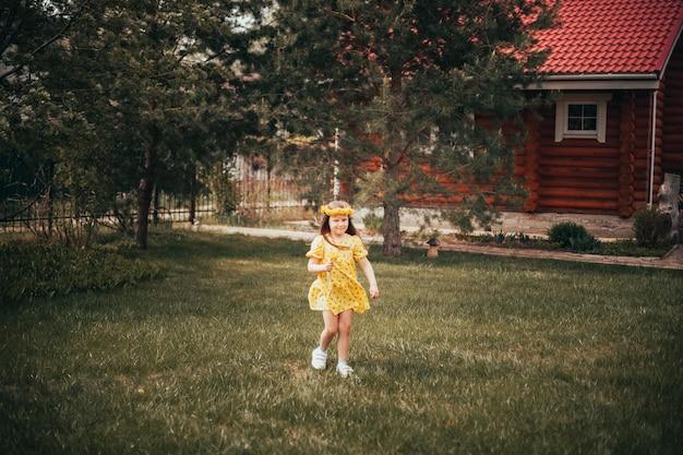 Lifestyle full-length portret van een kind dat op het gras in het bos rent op vakantie met zijn fam...