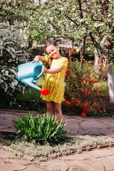 Lifestyle full-length portret van een lachend meisje in een gele jurk die bloemen water geeft uit een tuin wat ...