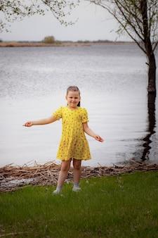 Lifestyle full-length portret van een meisje in een gele jurk op de rivieroever genietend van een warme lentedag...