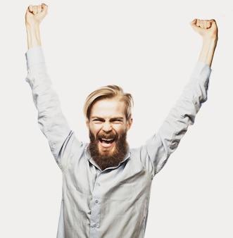 Lifestyle, geluk en mensen concept: jonge positiviteit bebaarde man hand opdagen tegen een grijze achtergrond.