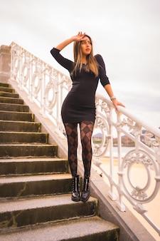 Lifestyle in de stad, blanke brunette in een korte zwarte jurk en geruite kousen genietend van de zomervakantie