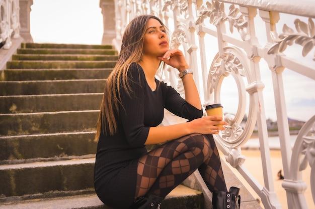 Lifestyle in de stad, blanke brunette in een korte zwarte jurk en met geruite panty's zittend genietend van de vakantie in de zomer