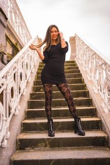 Lifestyle in de stad, poseren als een brunette blanke in een korte zwarte jurk en geruite kousen genietend van de zomervakantie