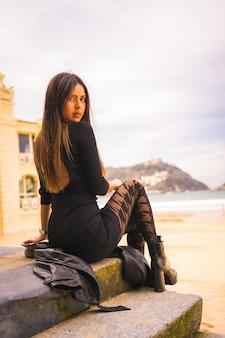 Lifestyle, kaukasische brunette zittend op een trap in een korte zwarte jurk, met een baret en geruite kousen naast een strand met uitzicht op zee