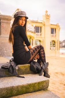 Lifestyle, kaukasische brunette zittend op een trap in een korte zwarte jurk, met een baret en geruite kousen naast een strand op vakantie in de zomer