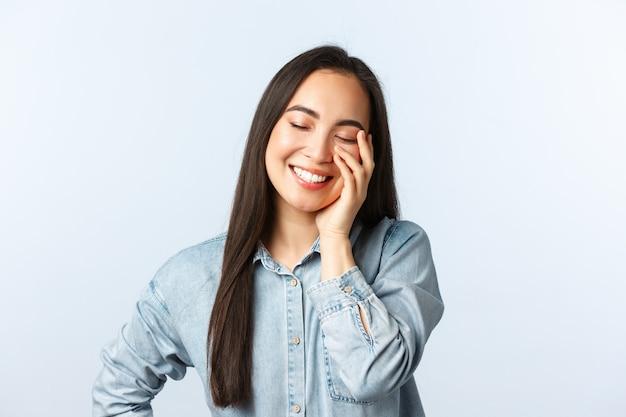 Lifestyle, mensen emoties en beauty concept. dromerig gelukkig mooi aziatisch meisje dat lacht, bloost en glimlacht met gesloten ogen, een schone huid aanraakt, witte achtergrond