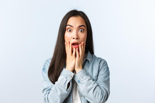 Lifestyle, mensen emoties en beauty concept. geschokte sprakeloze vrouwelijke aziatische student reageert op vreselijk eng nieuws, hijgend, laat de kaak vallen en staart bezorgd, hijgend verbaasd