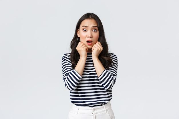 Lifestyle, mensen emoties en casual concept. bang bezorgd aziatisch meisje in gestreept shirt, hijgend kijkend gealarmeerd, in de problemen gekomen, ontdek schokkende waarheid, staande witte achtergrond