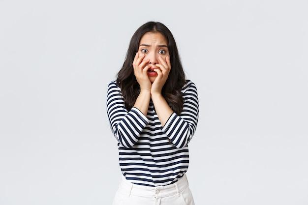 Lifestyle, mensen emoties en casual concept. bange timide en onzekere vrouw houdt handen in de buurt van de mond, schreeuwt en kijkt doodsbang, rillend van angst, staat op een witte achtergrond.