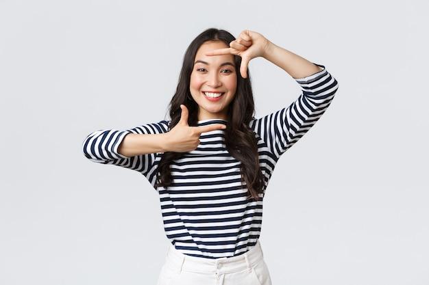 Lifestyle, mensen emoties en casual concept. creatief schattig aziatisch meisje dat zich voorstelt, moment vastlegt met handframes, geamuseerd glimlacht, positief en gelukkig blijft, witte achtergrond