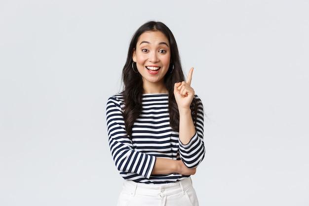 Lifestyle, mensen emoties en casual concept. opgewonden slimme en creatieve aziatische vrouwelijke collega heeft suggestie, voegt idee toe, steekt wijsvinger op om gedachte of plan te zeggen, staande witte achtergrond.