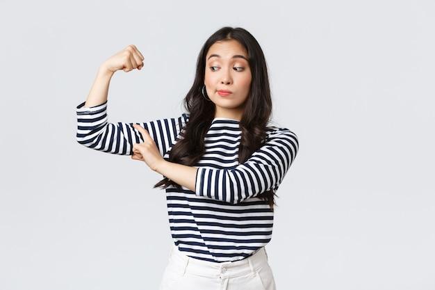Lifestyle, mensen emoties en casual concept. sterke en zelfverzekerde aziatische vrouw flex biceps, opscheppen over haar perfecte vorm na aanmelding sportschoollidmaatschap, opscheppen met spieren, trainen en zich sterk voelen