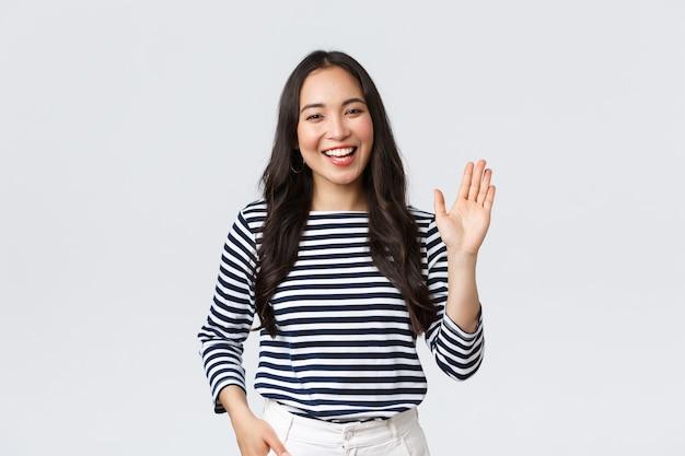 Lifestyle, mensen emoties en casual concept. vriendelijke vrolijke aziatische vrouw die lacht, hallo zegt en met de hand zwaait om persoon te begroeten, hallo gebaar te maken, iemand welkom te heten