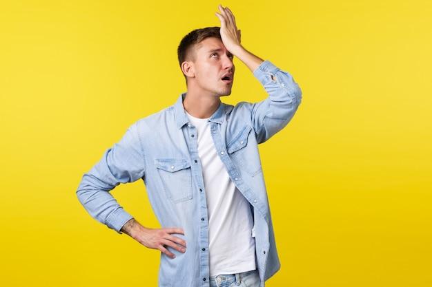 Lifestyle, mensen emoties en zomer vrije tijd concept. geërgerde en vermoeide blonde man slaat zichzelf in het voorhoofd en rolt met zijn ogen gehinderd, uitgeput om iets uit te leggen, gele achtergrond.