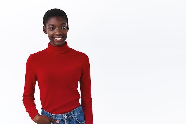 Lifestyle, mensen en bedrijfsconcept. jong vrolijk afrikaans amerikaans meisje in rode coltrui