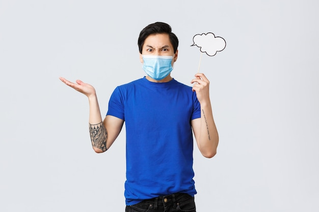 Lifestyle, mensen verschillende emoties en covid-19 pandemisch concept. boze man met medisch masker die vloekt en klaagt, hand ontzetting opheft, grimassen trekt, commentaarwolk bij het hoofd houdt