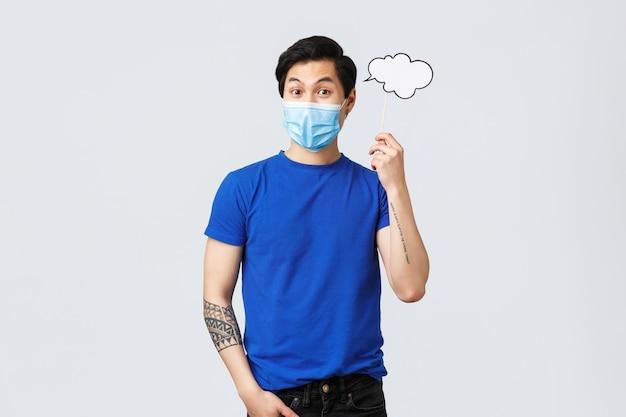 Lifestyle, mensen verschillende emoties en covid-19 pandemisch concept. verraste jonge aziatische man heeft een idee, draagt een medisch masker en houdt een commentaarwolk bij het hoofd, een bedenkoplossing