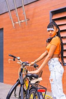 Lifestyle met een jonge trapdanseres in de stad. zwart grindmeisje van afrikaanse etnische groep met oranje overhemd in de stad. cofing fiets geparkeerd in de stad, glimlachend