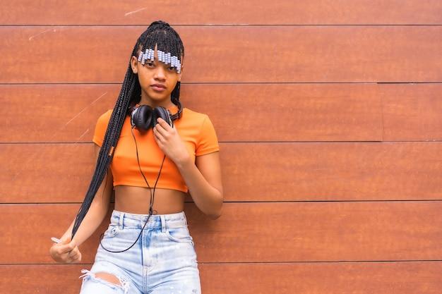 Lifestyle met een jonge trapdanseres in de stad. zwart grindmeisje van afrikaanse etnische groep met oranje t-shirt en cowboybroek, met koptelefoon op een houten achtergrond