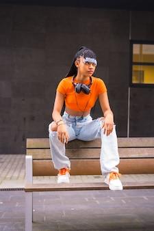 Lifestyle met een jonge trapdanseres in de stad. zwart grindmeisje van afrikaanse etnische groep met oranje t-shirt en cowboybroek, met koptelefoon op een zwarte achtergrond