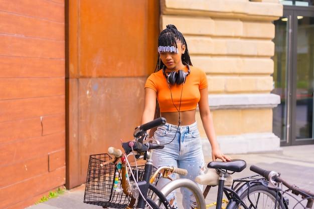 Lifestyle met een jonge trapdanseres in de stad. zwart meisje van afrikaanse etnische groep met oranje t-shirt en cowboybroek. de fiets in de stad parkeren bike